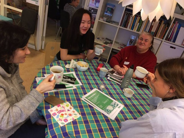 Fyra kvinnor sitter vid ett bord och pratar och dricker kaffe