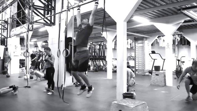 Svartvit bild på personer som tränar i ett crossfit-gym