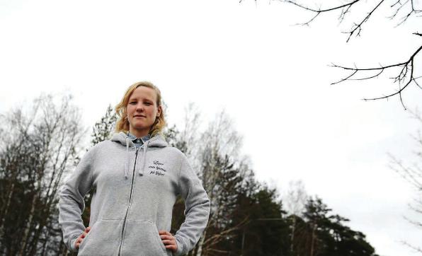 Stina Odlingson står utomhus i grå hoodie och tittar in i kameran med händerna på höfterna