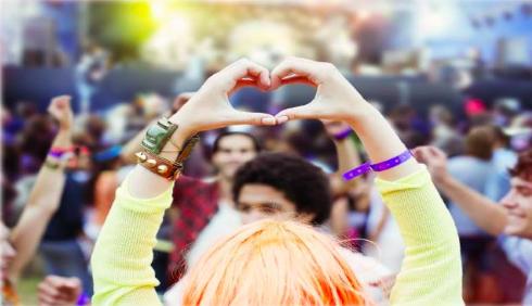bild på folkmassa, närmast kameran formar en tjej i gul tröja ett hjärta med sina händer.